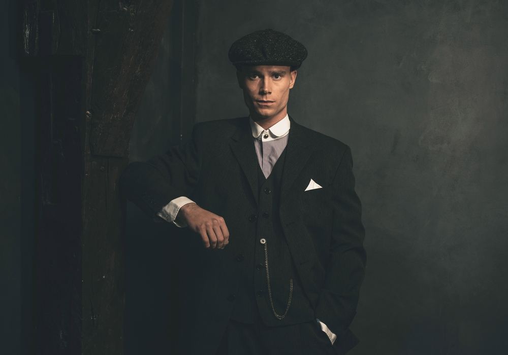 Retro 1920s english gangster wearing suit and flat cap.