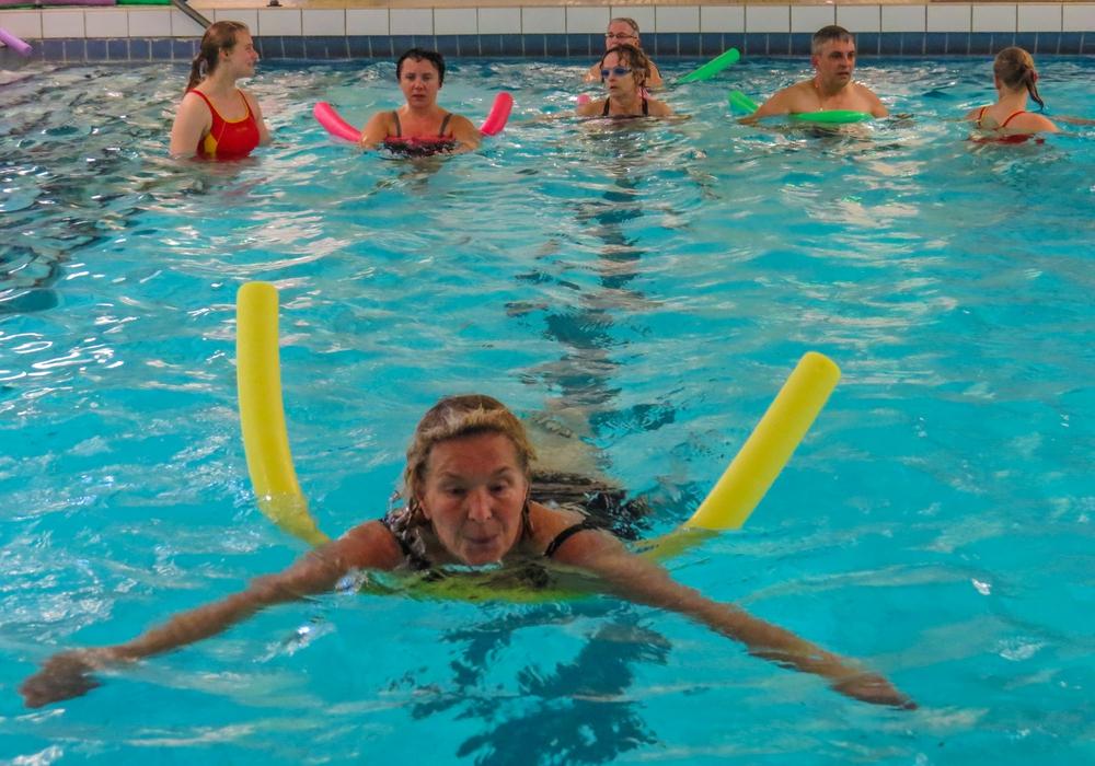 Mit einer Schwimmhilfe lernen die Erwachsenen die sorgfältigen Schwimmbewegungen. Fotos: DLRG
