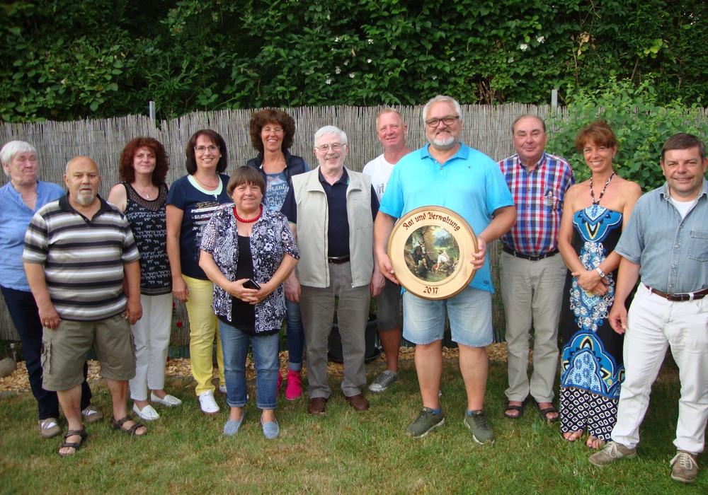 Rüdiger Bobka (mit Scheibe) inmitten von Ratsmitglieder und Gästen. Foto: Gemeinde Schöppenstedt