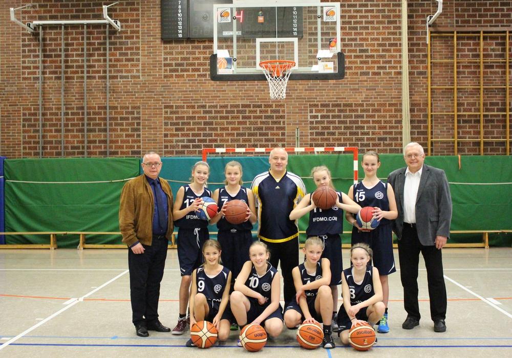 Die U-13 Mädchenmannschaft sowie der Trainer Thorsten Weinhold (Mitte) freuen sich über die gespendeten Basketbälle des Fördervereins. Hier vertreten durch den stellvertretenden Vorsitzenden Andreas Meißler (links) und dem Vorsitzenden Klaus Hantelmann (rechts). Foto/Video: Max Förster