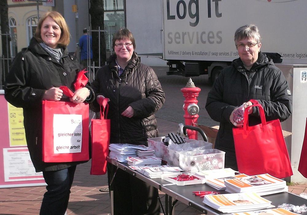 Birgit Grimm, Christine Scholz und Marion Meyer vom SoVD Kreisverband Gifhorn verteilen rote Taschen, die sinnbildlich auf die roten Zahlen in den Geldbörsen von Frauen hinweisen. Foto: SoVD Gifhorn.