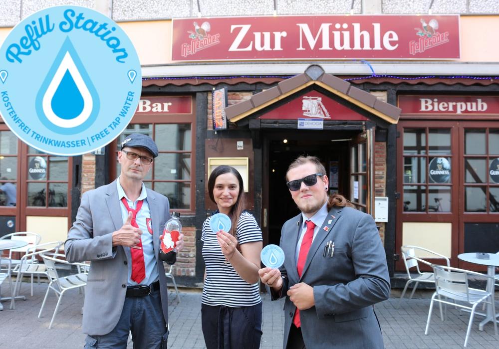 Jamie Christopher Lodge (rechts im Bild) und Lutz Kiehne (links im Bild) überreichen Natalja Klobertanz (Bildmitte) von der Gaststätte Zur Mühle die ersten Refill-Aufkleber. Foto: DIE PARTEI