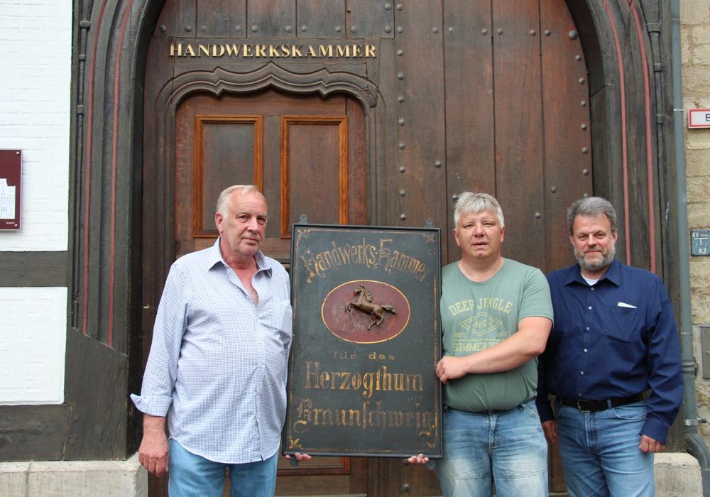 Karl Fischer, Reiner Becker und Dr. Thomas Felleckner mit dem alten Namensschild  vor dem Eingang der Kammer am Burgplatz (v. li.). Foto: Handwerkskammer Braunschweig-Lüneburg-Stade