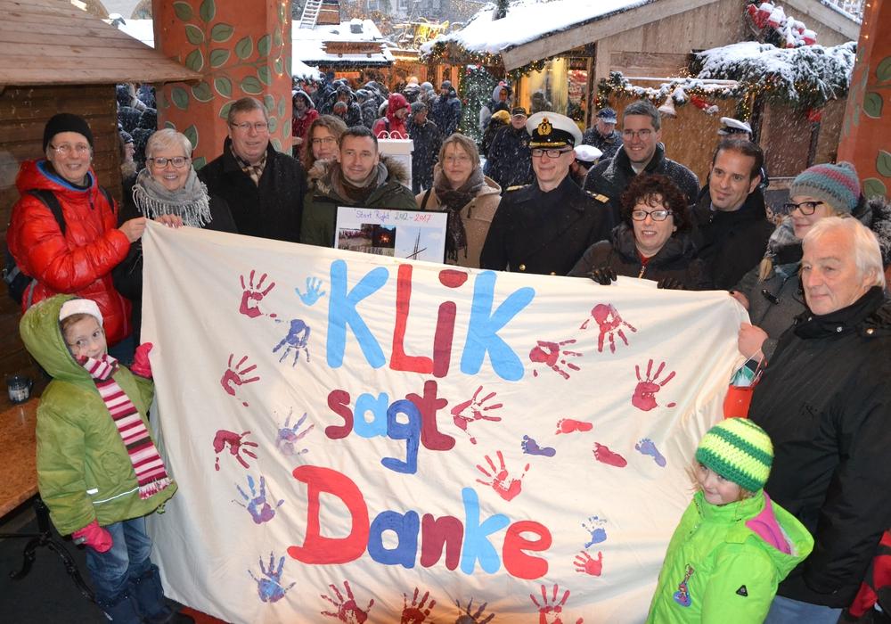 """Beim Glühweinstand unter den Arkaden wurde die Spende an """"KliK"""" übergeben. Foto: Stadt Goslar"""