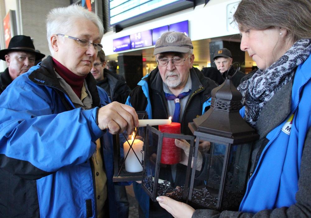 Marita Pongratz von der Deutschen Pfadfinderschaft St. Georg gibt das Friedenslicht weiter an eine Mitarbeitern der Bahnhofsmission. Foto: Max Förster