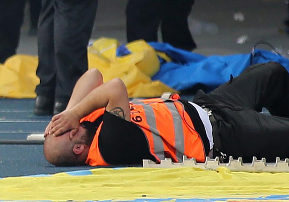 Ein Ordner liegt am Boden, wurde von einem Knallkörper getroffen. Er wurde leicht verletzt. Foto: Agentur Hübner
