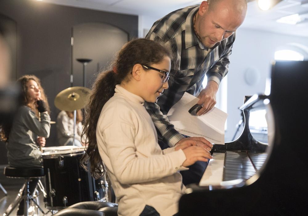 Musik-Dozent Mirko Böhm bringt den Kindern Lieder ohne Noten bei. Foto: Volksbank BraWo/Peter Sierigk