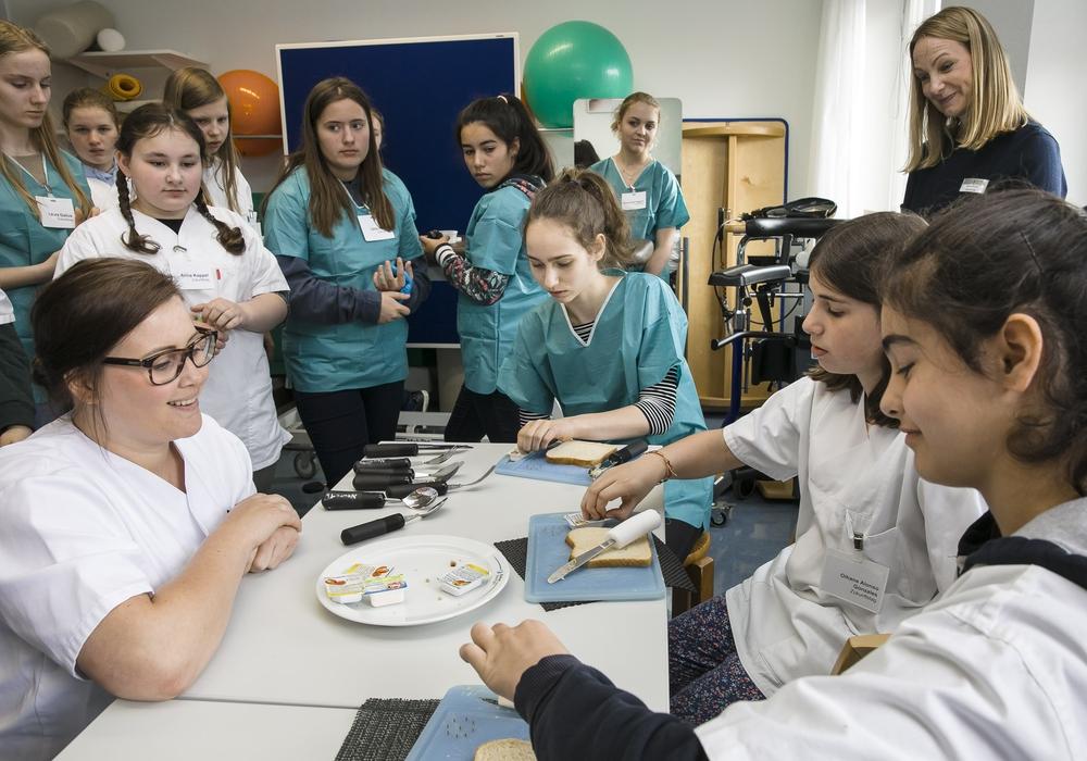 Ergotherapeutin Mona Bachmann (links) erklärt, wie Schlaganfall-Patienten lernen, ein Brot mit nur einer Hand zu schmieren. Klinikum. Fotos: Braunschweig/Peter Sierigk