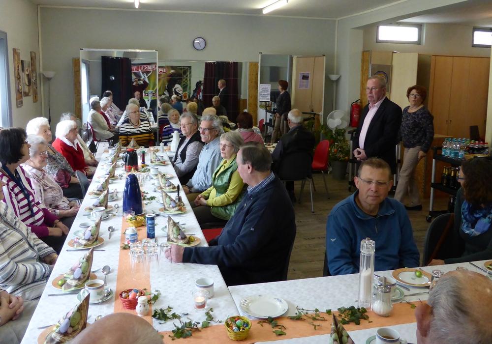 Der österlich gedeckte AWO-Tisch mit zahlreichen Teilnehmern während der Begrüßungsworte von Hans-Joachim Kröger. Im Hintergrund Hannelore Schweigel vom Helferteam. Foto: AWO