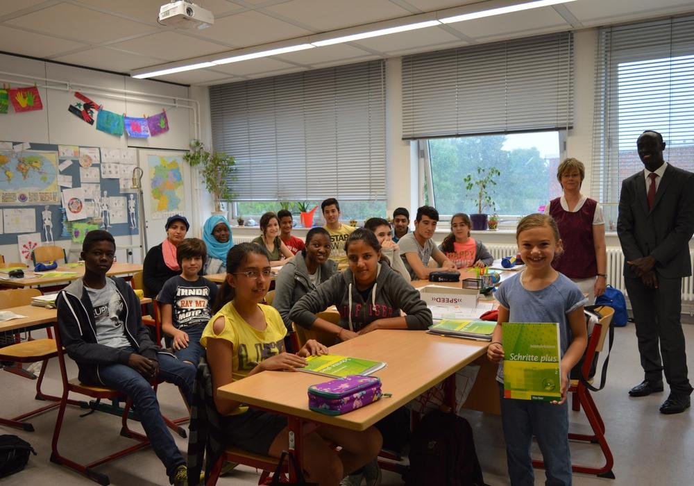Im Bild rechts: Ida Schuchhardt spendet Lehrbücher. Dahinter: Lehrerin Cora Kruse und Dolmetscher Samuel Serefino. Foto: Margit Richert