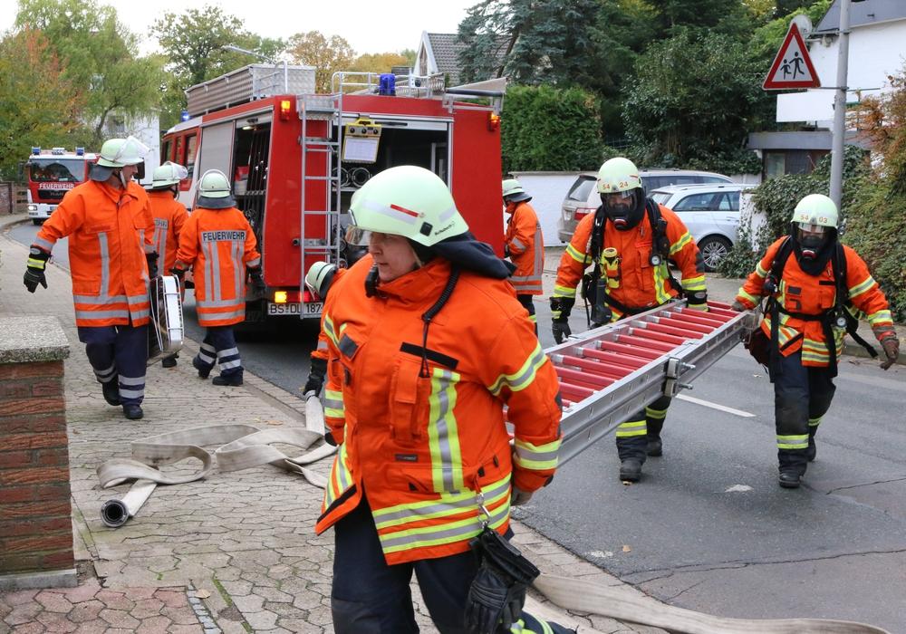 Die Einsatzkräfte tragen eine Leiter zur Rettung einer verletzten Person an die Einsatzstelle. Auch die Atemschutzgeräteträger packen mit an. Fotos: Werner Heise / Jonathan Heise