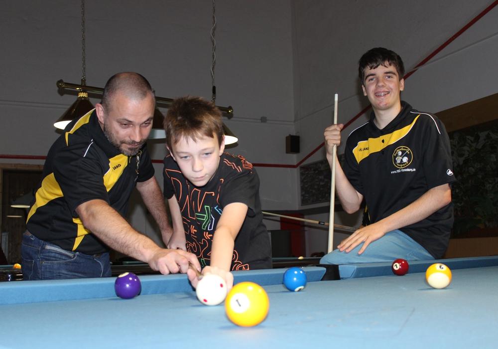 Der Pool Billard Sport Club Vienenburg beteiligte sich auch in diesem Jahr mit einer Aktion am Ferienpass der Stadt Goslar. Jugendtrainer Tobias Dahnke und Jugend-Mitglied Leon zeigen Ferienkind Hauke, wie man die Kugel einlocht. Fotos: Anke Donner