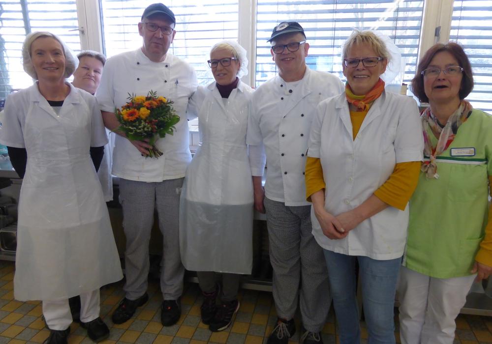 """Der """"20-jährige-Dienstjubilar"""" Frank Hahne mit Blumenpräsent im Kreise seiner Kolleg*innen in der SchloßkücheFoto: Sabine Resch-Hoppstock"""