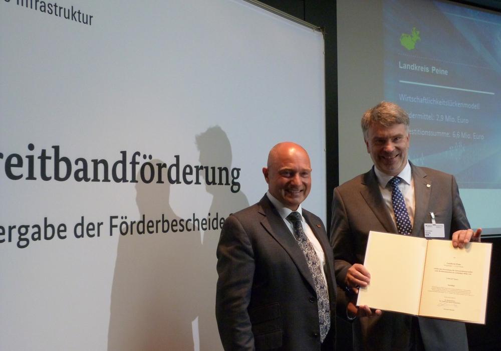 Kreisrat Henning Heiß nahm den Förderbescheid aus den Händen von Staatssekretär Rainer Bomba entgegen. Foto: Büro Heil