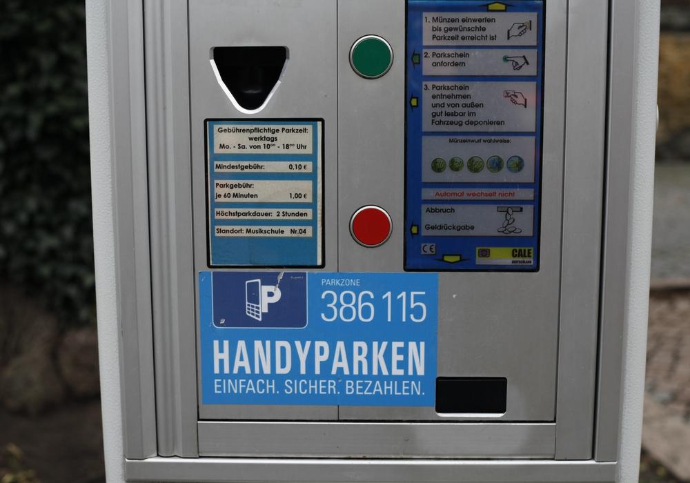 Aufkleber auf Parkautomaten weisen auf die Möglichkeit hin, auch per Handy Parkzeit zu buchen. Foto: Alec Pein