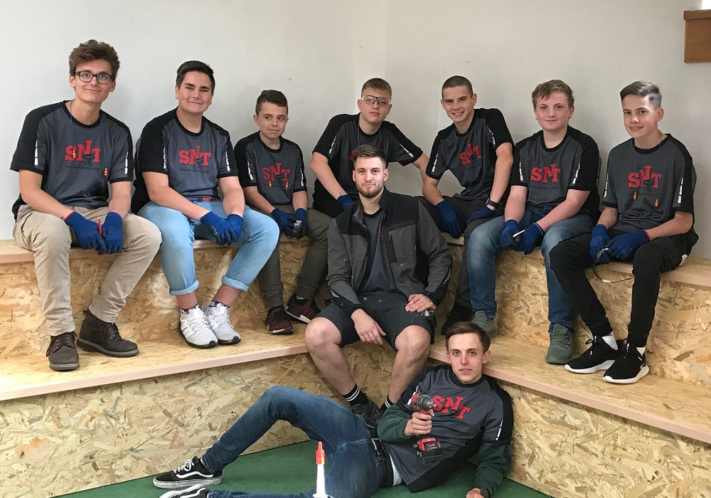Die acht Schüler der IGS Wallstraße und Tischlergeselle Phil Geffers von der Tischlerei SNT auf der fertigen Ecksitzbank. Foto: Tischlerei SNT