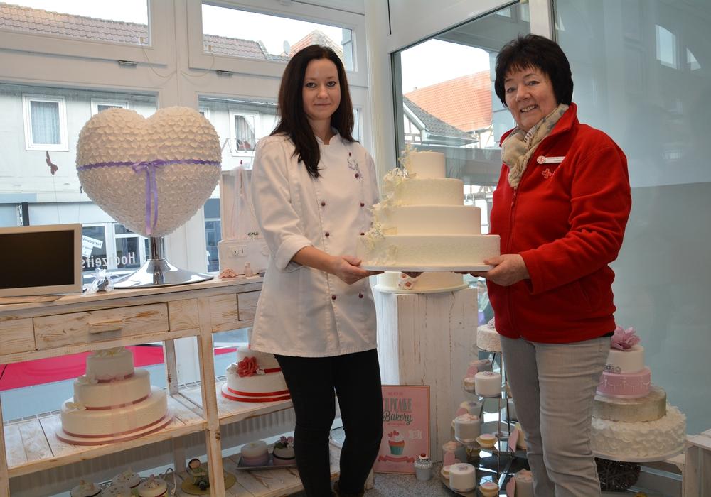 Anna Buchholz (links) überreicht in ihrem Geschäft an der Breiten Herzogstraße eine Hochzeitstorte an Juliane Liersch, die Leiterin des DRK-Tafelladens in Wolfenbüttel. Foto: DRK