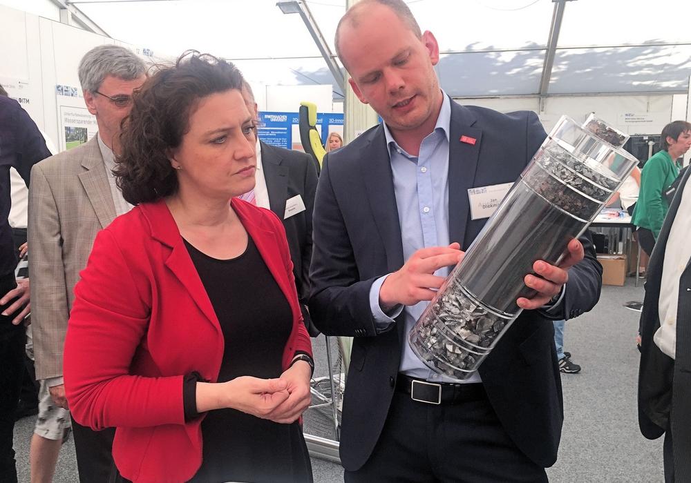 """Mit einer """"Gläsernen Batterie"""" zeigt Jan Diekmann der TU Braunschweig Carola Reimann, welche wertvollen Materien sie mit dem """"LithoRec""""- Recyclingprozess aus einer Lithium-Ionen-Altbatterie zurückgewinnen können und wie sie damit einen Beitrag zu einer nachhaltigen Elektromobilität sowie zur Verringerung der geostrategischen Abhängigkeit von wichtigen Rohstoffen leisten. Foto: Privat"""