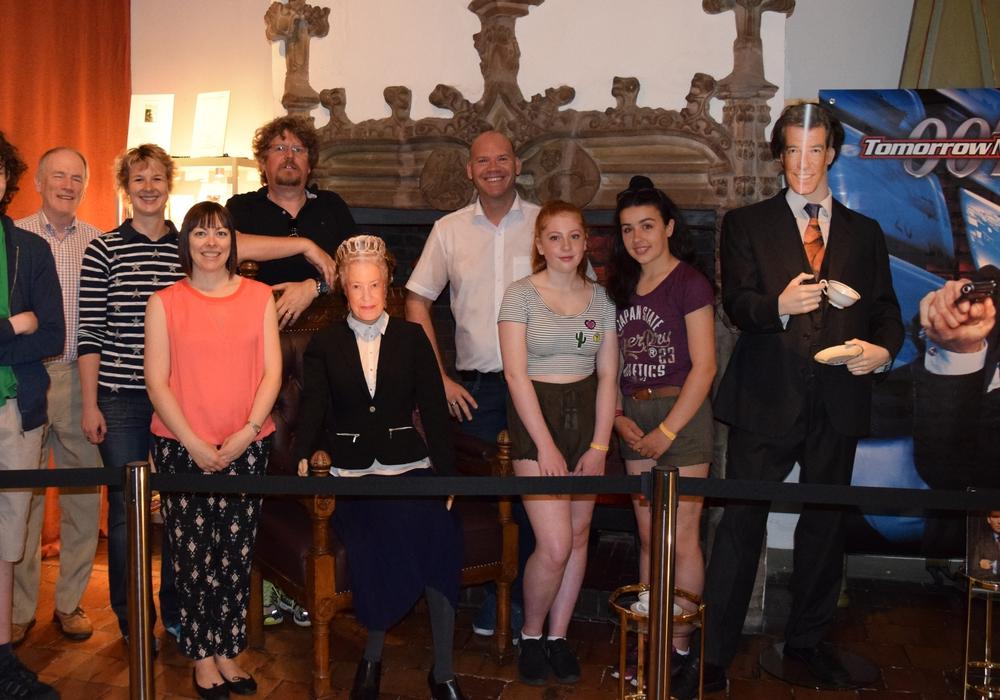 Begeistert von der James-Bond-Ausstellung posieren die drei Schüler mit Bürgermeister Mahnkopf (Mitte) und ihren begleitenden Lehrkräften neben der Queen und Pierce Brosnan. Fotos: Stadt Goslar