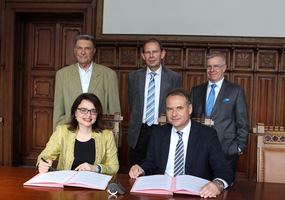 Alessandra Buganè und Oberbürgermeister Ulrich Markurth beim Unterzeichnen des Vertrages. Hinter ihnen von links: Karl Milkau, Gefried Sommer und Claus Ruppert. Foto: Nick Wenkel