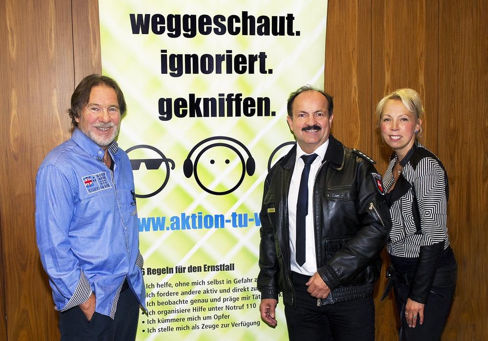 Götz George, Günter Koschig (Projektleiter) und Heike Göttert (Aktionsfotografin) vor dem Aktionsbanner der Goslarer Zivilcouragekampagne. Foto: Polizei Goslar