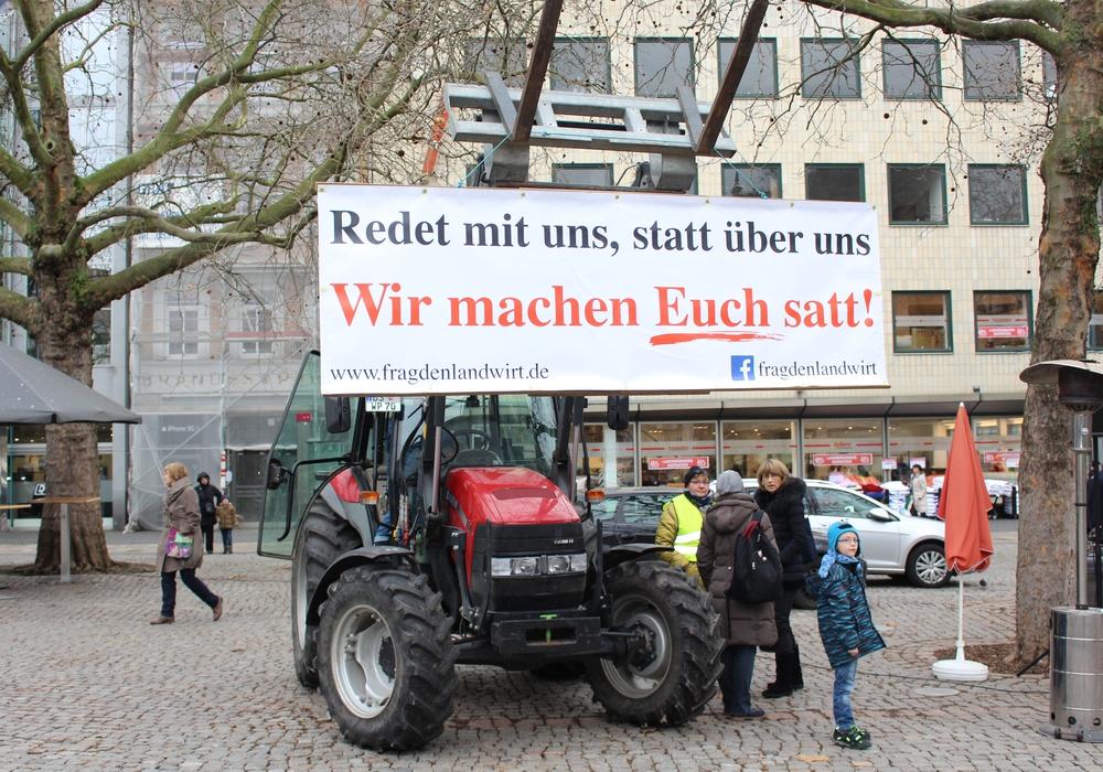 """""""Redet mit uns, statt über uns – Wir machen satt"""" steht auf dem Plakat, das die Landwirte an einen Trecker mitten auf dem Kohlmarkt hangen. Fotos: Jan Borner"""