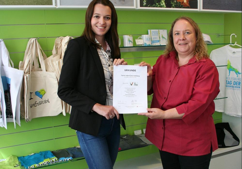 """Stephanie Möller(links) und Susanne Große-Freese präsentieren die Urkunde der Qualitätsinitiative """"Reisen für Alle"""" in der Wolfsburger Tourist-Information. Foto: WMG Wolfsburg"""