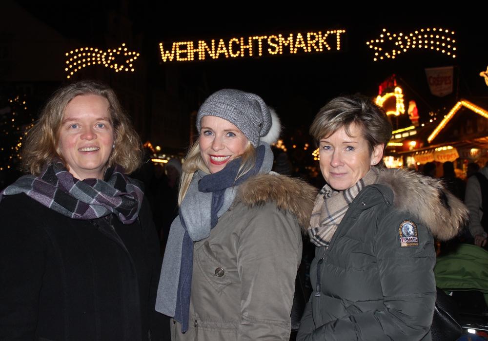 Vera Steiner, Corinna Düe und Kerstin Hecker vor dem beleuchteten Weihnachtsmarkt. Foto: Anke Donner