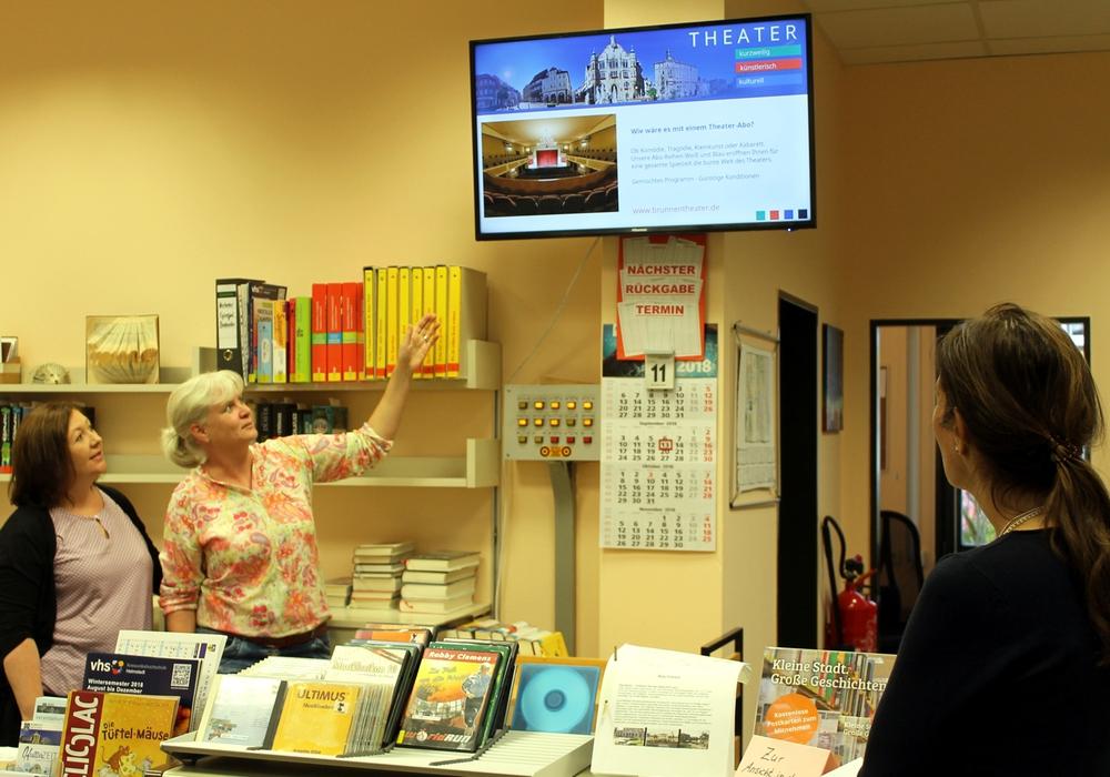 v.l.: Irina Hoffmann, Yvonne Bowman und Karen Zingel aus der Stadtbücherei freuen sich über den neuen Monitor, der die Besucher über Termine und Angebote in der Stadt informiert. Foto: Stadt Helmstedt