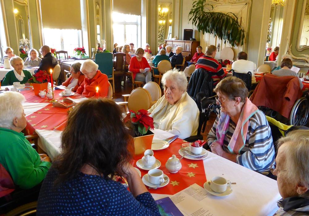 Die Vertreterinnen der Frauenhilfe mit den Bewohnern im adventlich geschmückten Spiegelsaal der Seniorenbetreuung Schloß Schliestedt. Foto: Privat