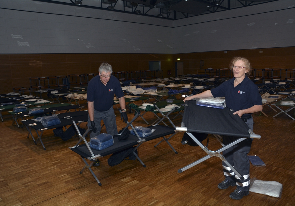 Detlef und Christiane Pottgießer richten in der Lindenhalle  zwei von 150 Feldbetten her.  Foto: DRK