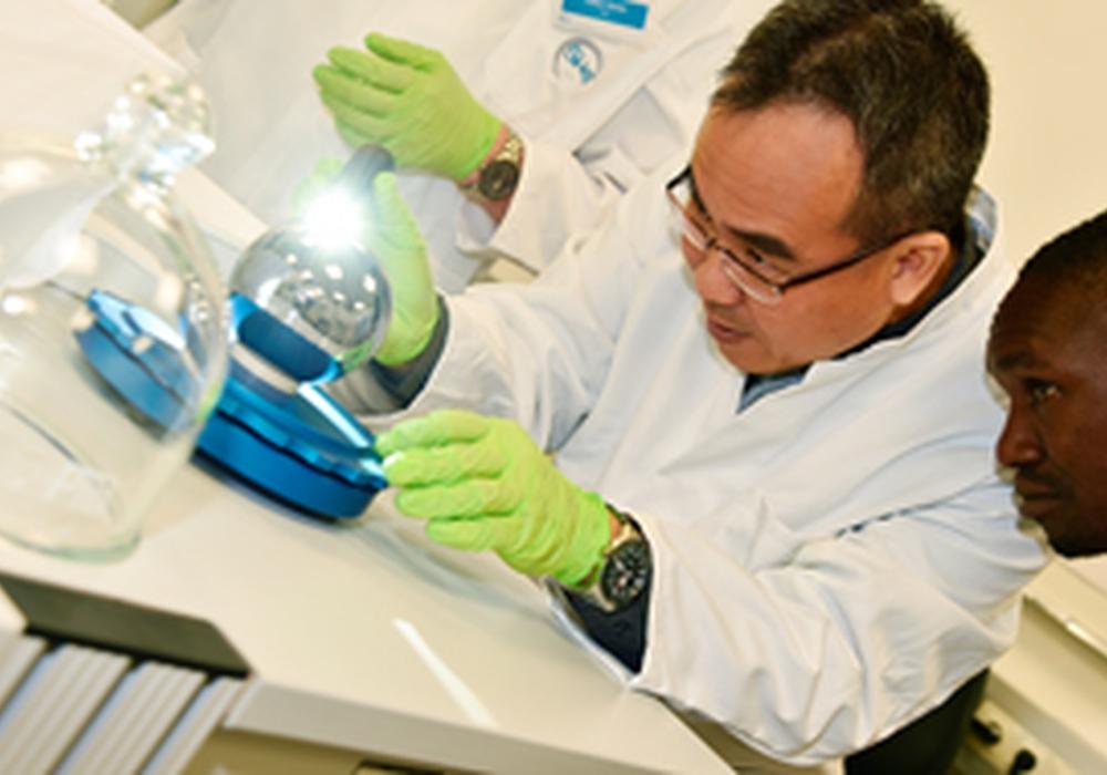 Shih Mean Lee (NMC, Singapur) und Wilson Ombati (KEBS, Kenia) überprüfen, ob sich Staubpartikel auf der Si-Kugel befinden. Foto: PTB