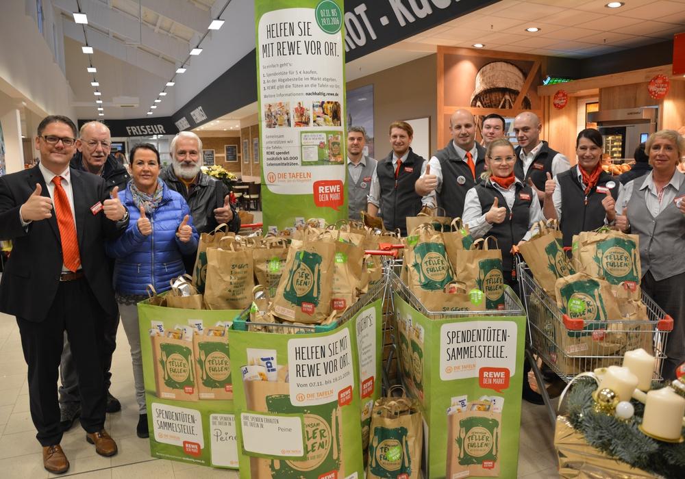 Die spendenfinanzierten Tüten wurden im REWE-Markt an die Vertreter der Tafel übergeben Foto: REWE