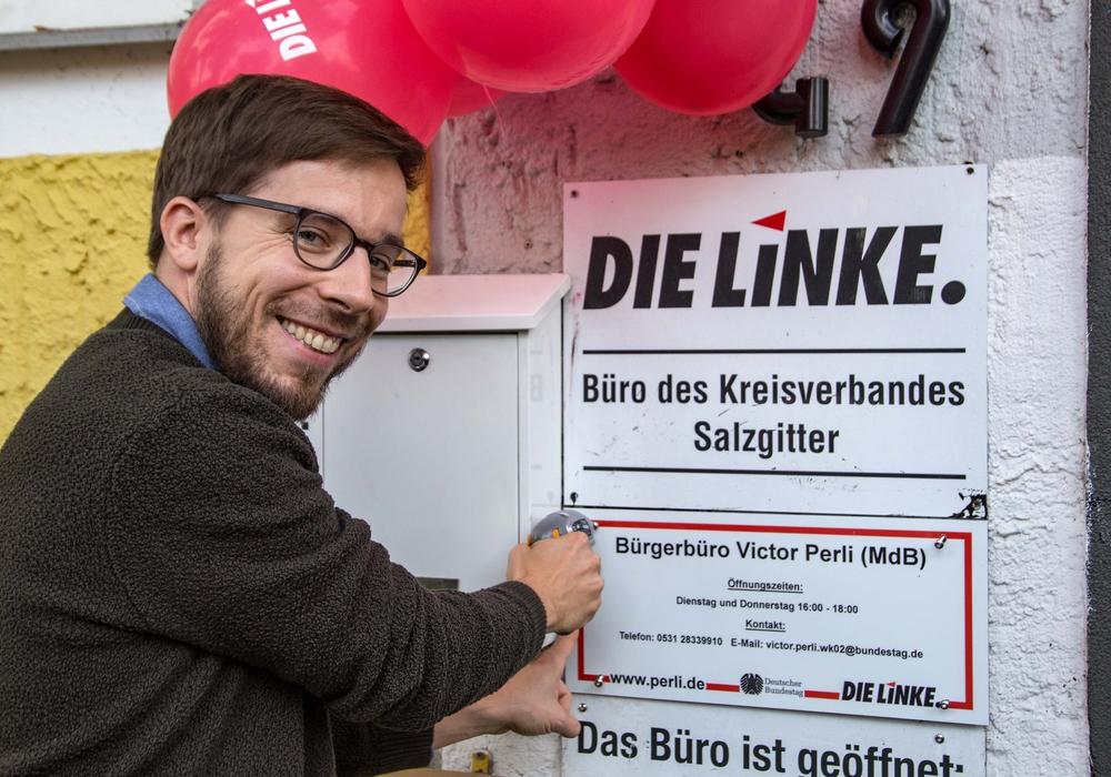 Viktor Perli schraubt feierlich das Schild an das neue Bürgerbüro. Foto: Rudolf Karliczek