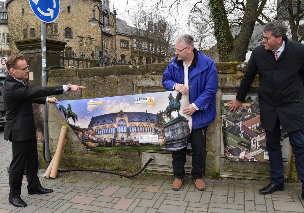 Die Goslarer Kaiserpfalz, die Frank Uhlenhaut und Frank Koschnitzke, Creativ Director der ausführenden Firma Koschi & Co, hochhalten, ist immer noch das eindrucksvollste, findet Dr. Oliver Junk (von links). Foto: Stadt Goslar