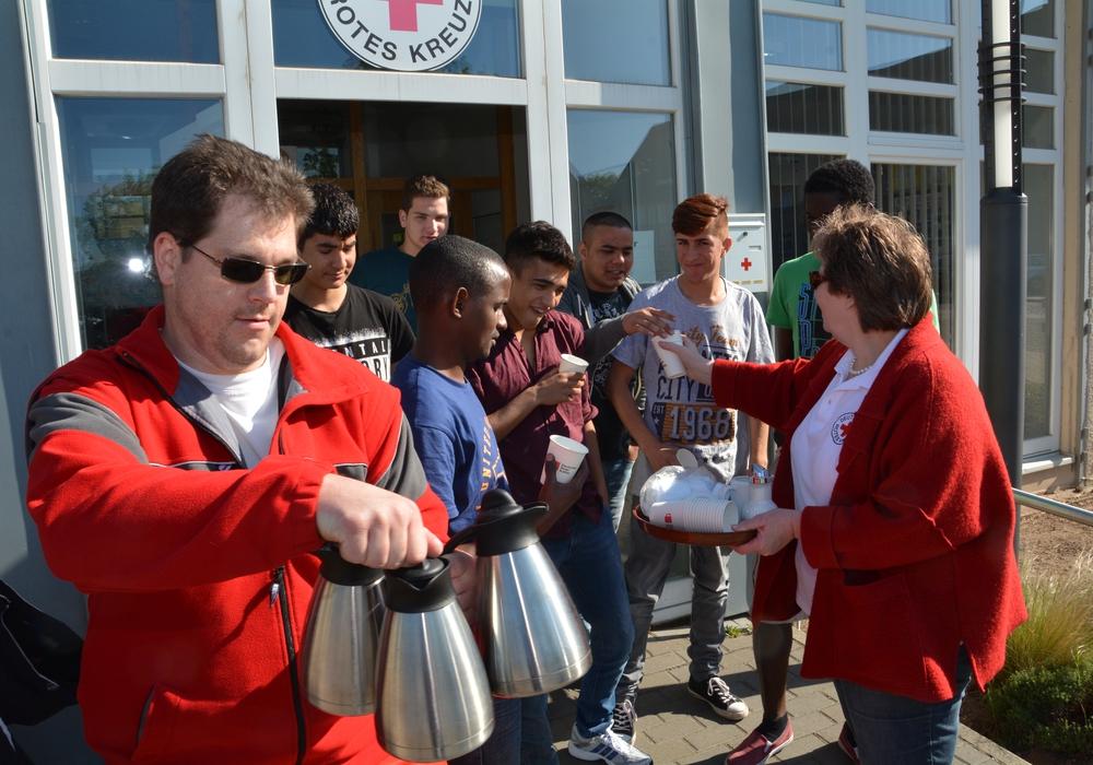 Thorben Wohlt (links in rot) und Heike Hintze verteilten vor dem Solferino am Exer Kaffee. Hier kommen die Teilnehmer des Sprachkurses für Flüchtlinge in den unverhofften Genuss. Foto: DRK