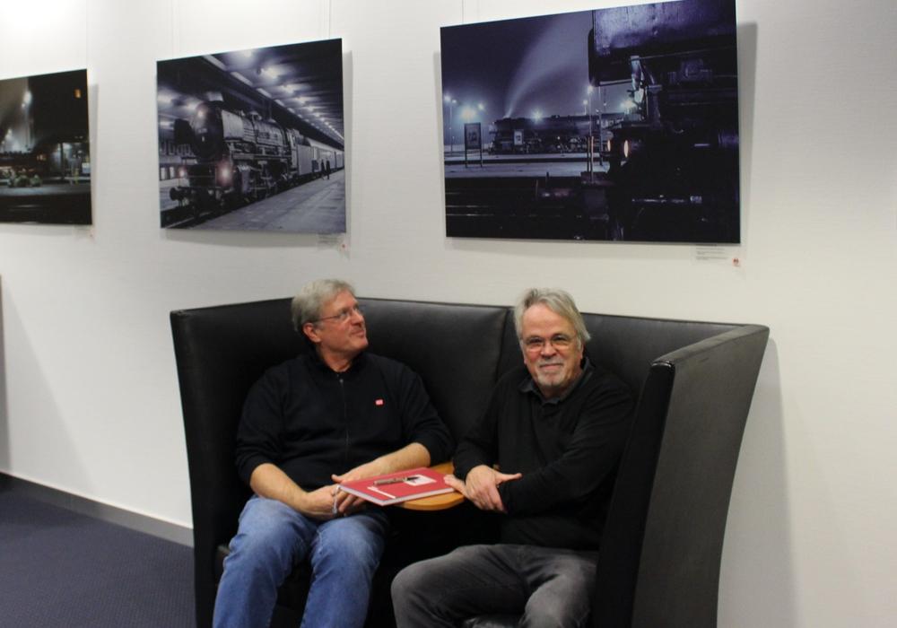 Christian Ernst (links) und Hans-Georg Ahrens betrachten die Eisenbahnfotos. Foto: Frederick Becker