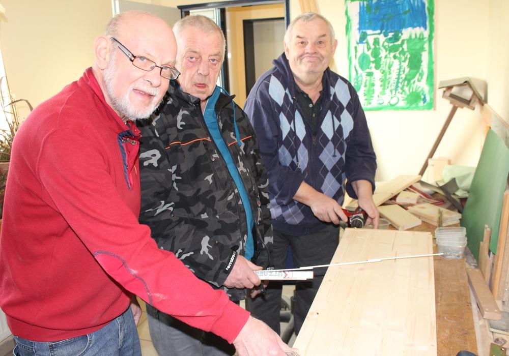 Roland Wolff, Ehrenamtlicher in der Lebenshilfe, bereitet mit den Bewohnern Rolf Busse und Eberhard Walter die Holzplatte zum Zuschnitt vor. Fotos: Privat