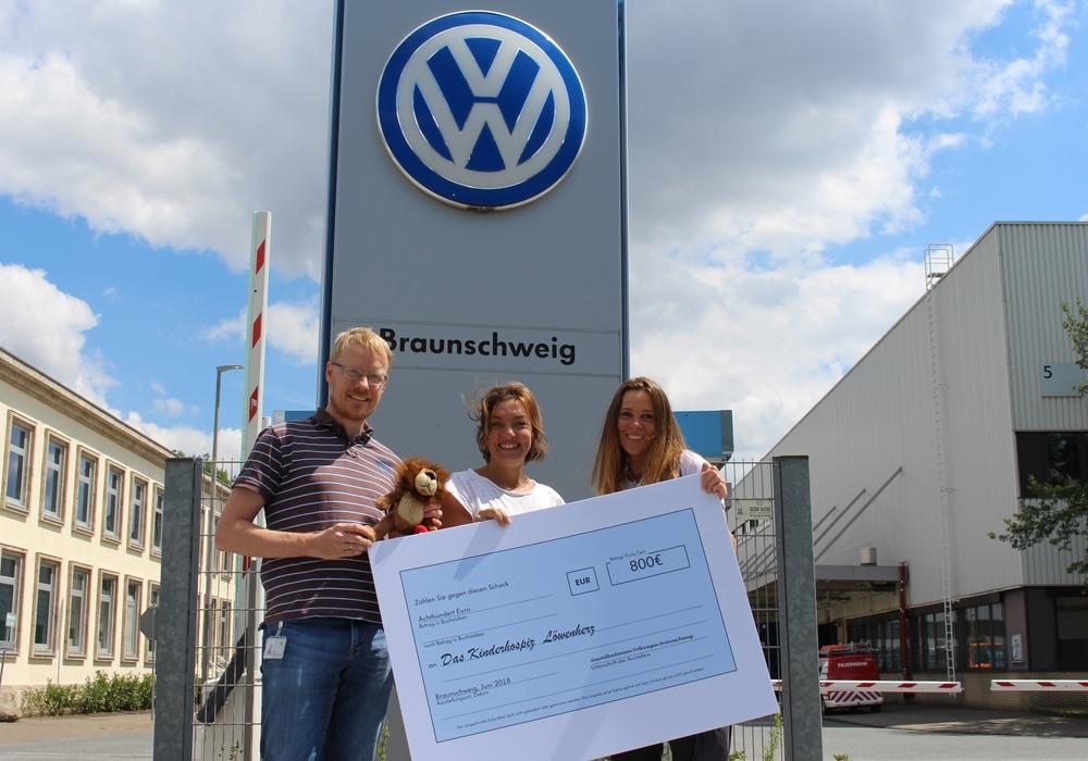 Die Volkswagen-Mitarbeiter Jan Voigt (links) und Katja Saathoff (rechts) bei der symbolischen Scheckübergabe an Isa Groth vom Kinderhospiz Löwenherz. Foto:  Volkswagen AG