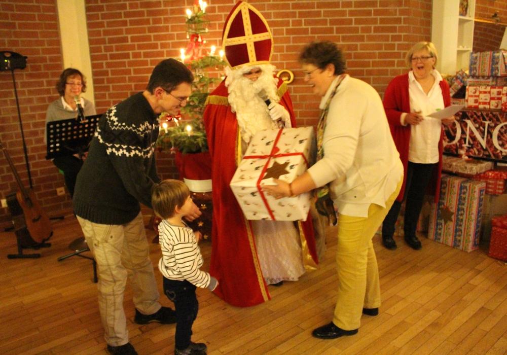 Die vierjährige Lisa-Marie nimmt mit Hilfe ihres Papas ein großes Paket vom Weihnachtsmann und seinen Helferinnen entgegen. Fotos: Alexander Dontscheff