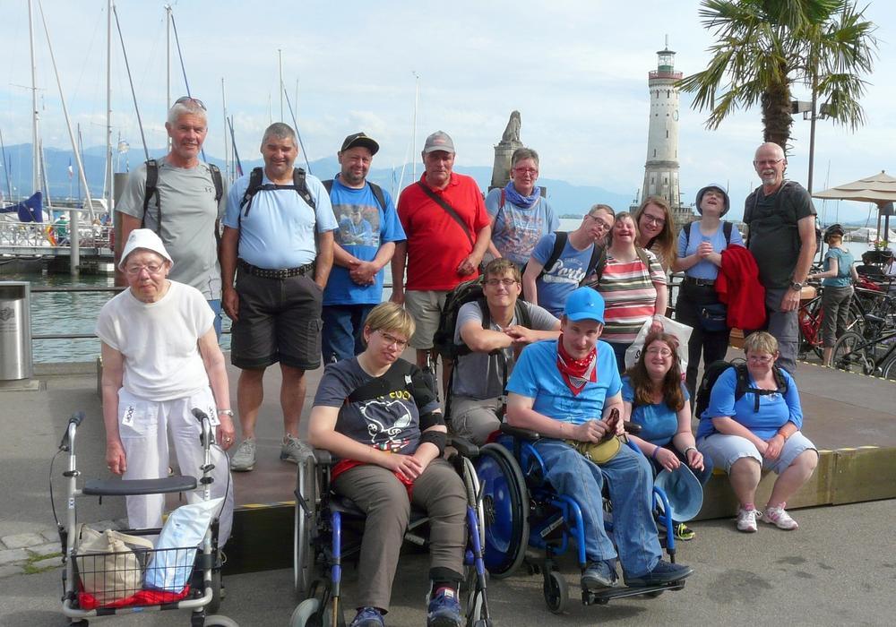 Eine Reisegruppe posiert am Bodensee. Im Hintergrund ist der Leuchtturm von Lindau. Foto: Privat
