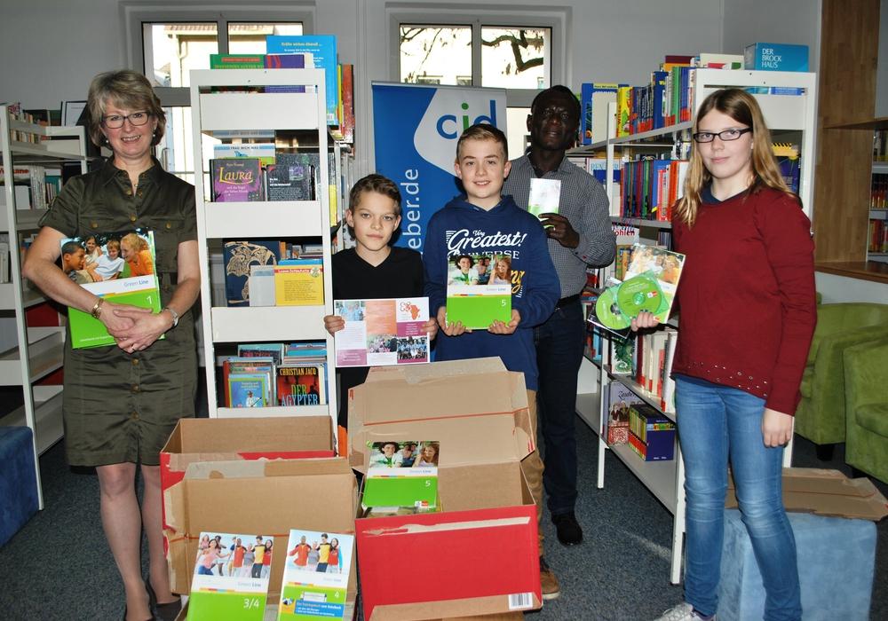 Colette Drescher, Owusu Agyei und Schüler des Gymnasiums mit der Lernmaterialspende in der Schulbibliothek. Foto: Privat