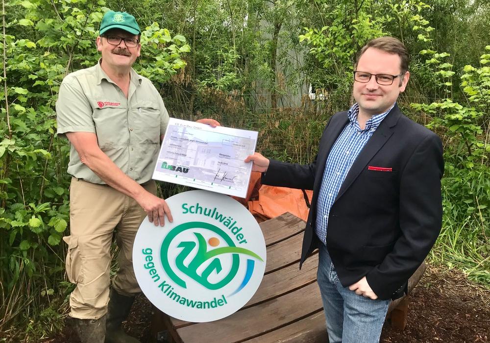 """Sven Hansmeier (rechts) überreichte einen symbolischen Scheck über 10.000 Euro an Franz Hüsing, Direktor von """"Zukunft Wald"""", einer Stiftung der Niedersächsischen Landesforsten. Foto: FIBAV"""