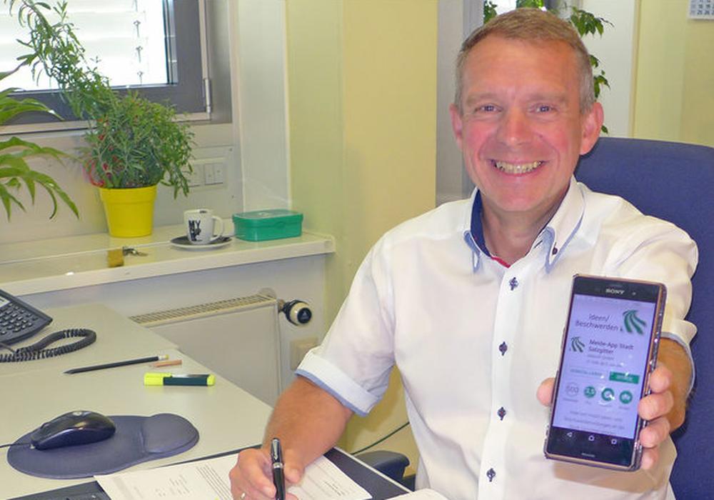 Carsten Bauerochse präsentiert auf einem Smartphone die Ideen- und Beschwerde-App der Stadt Salzgitter. Foto: Stadt Salzgitter