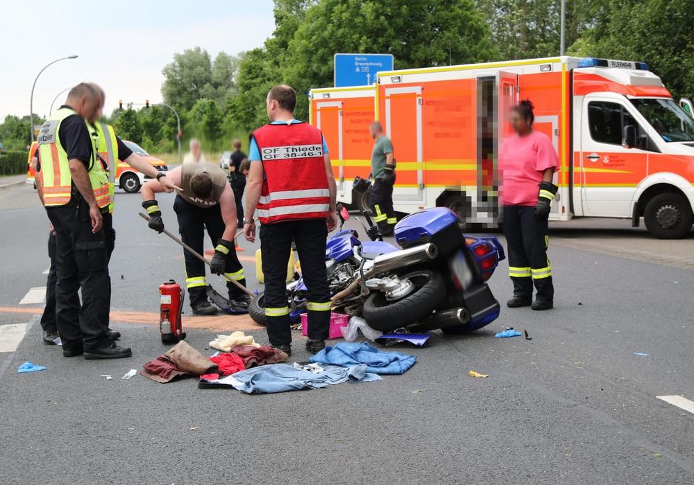 Während der verletzte Fahrer im Rettungswagen liegt, räumt die Feuerwehr bereits die Straße auf. Foto: Rudolf Karliczek