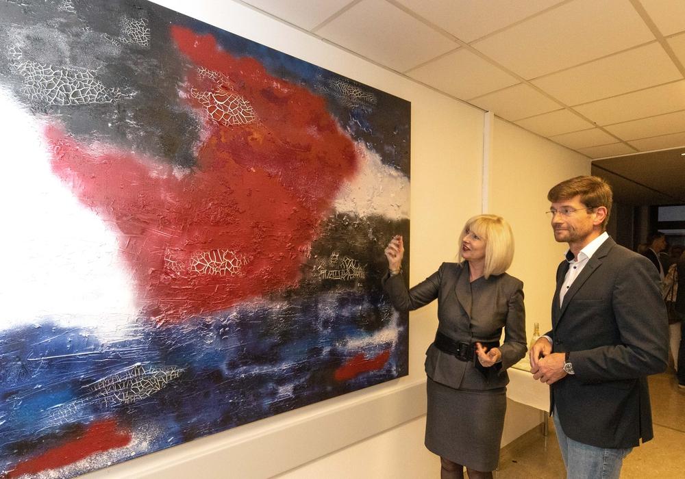 Künstlerin Marion Dollenberg (links) präsentiert eines ihrer Bilder. Foto: Rudolf Karliczek