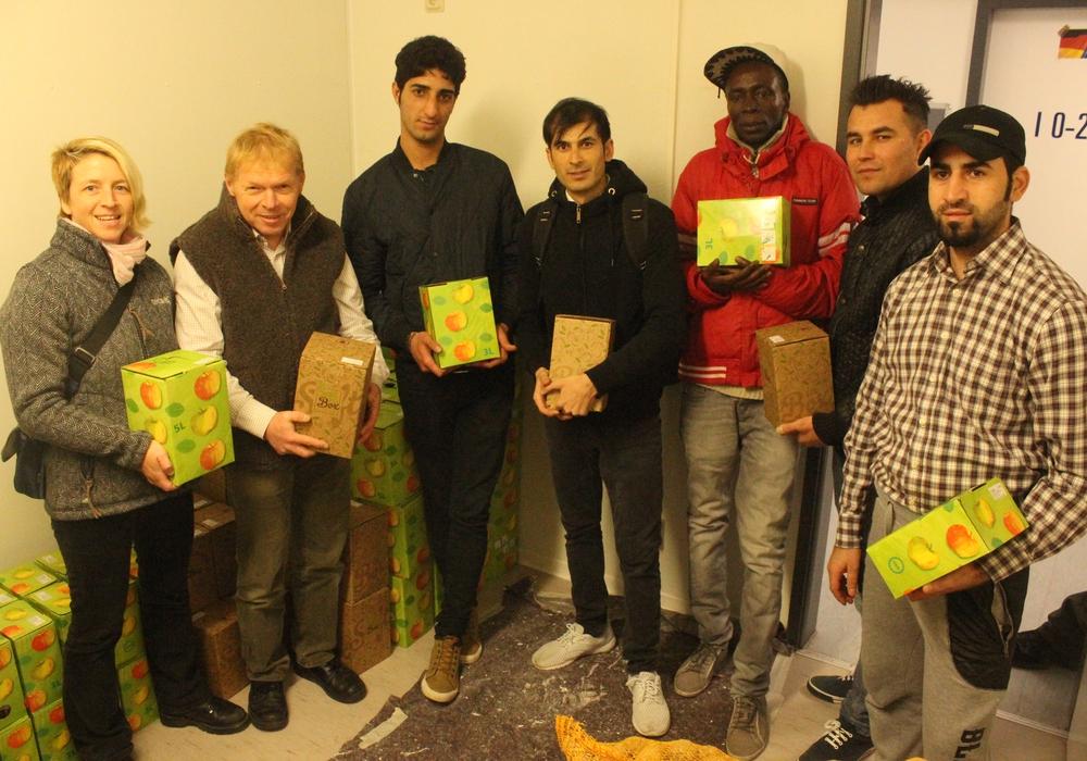 Beate Zgonc, Olaf Dalchow und einige Bewohner der Unterkunft bei der Übergabe der Apfelsaft-Boxen. Foto: Anke Donner