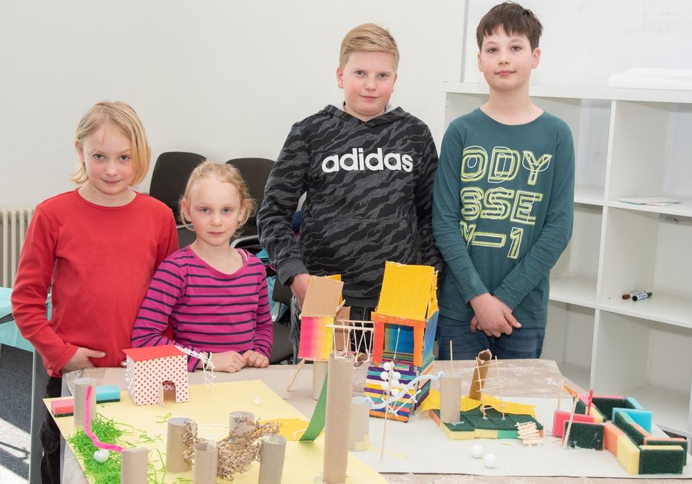 Die zehnjährige Selina, die siebenjährige Elize, der elfjährige Julian und der elfjährige Theo mit ihren gebastelten Spielplatz-Modellen (v. li.). Foto: Tanja Bischoff