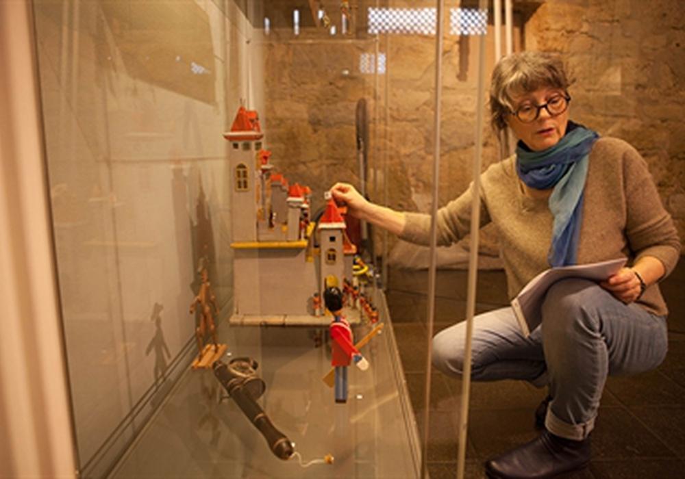 "Doris Schulz-Wahle beim Aufbau der Ausstellung ""Kinderträume aus buntem Holz"". Foto: Stadtmuseum Schloss Wolfsburg/Peter Riewaldt"