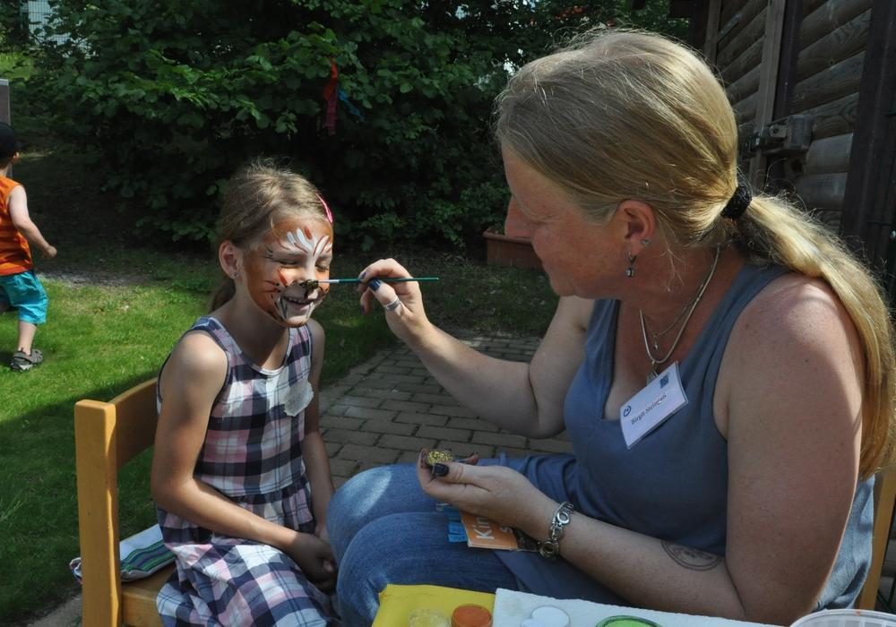 Frühförderin Birgit Steingaß schminkte Fest-Besucherin Julia ein Löwengesicht. Fotos: Lebenshilfe